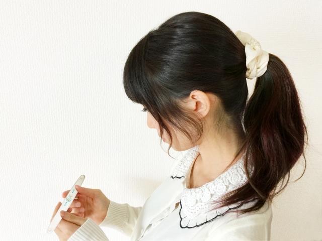 妊娠検査キットを見る女性