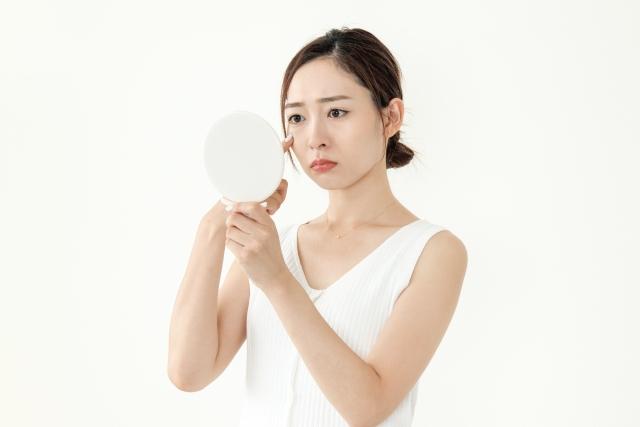 手鏡で自分の顔をみる女性